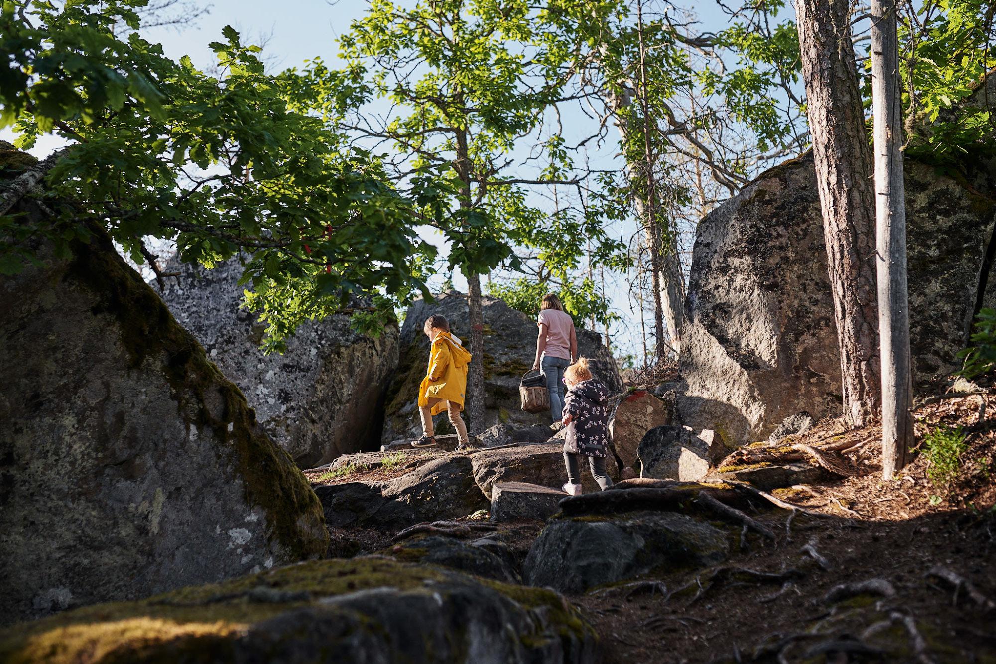 Vuxen och två barn går uppför sluttning bland stenar